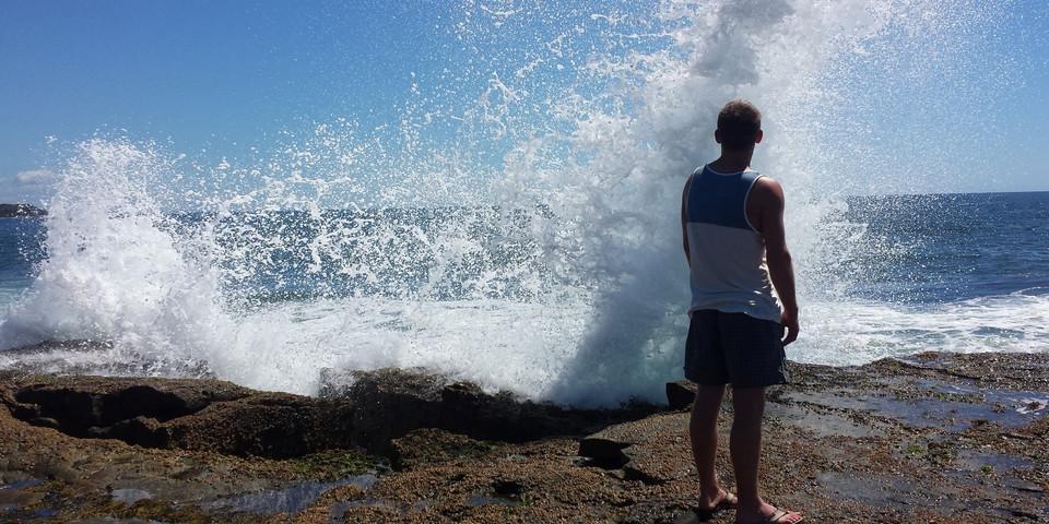 Junger Mann steht am Meer