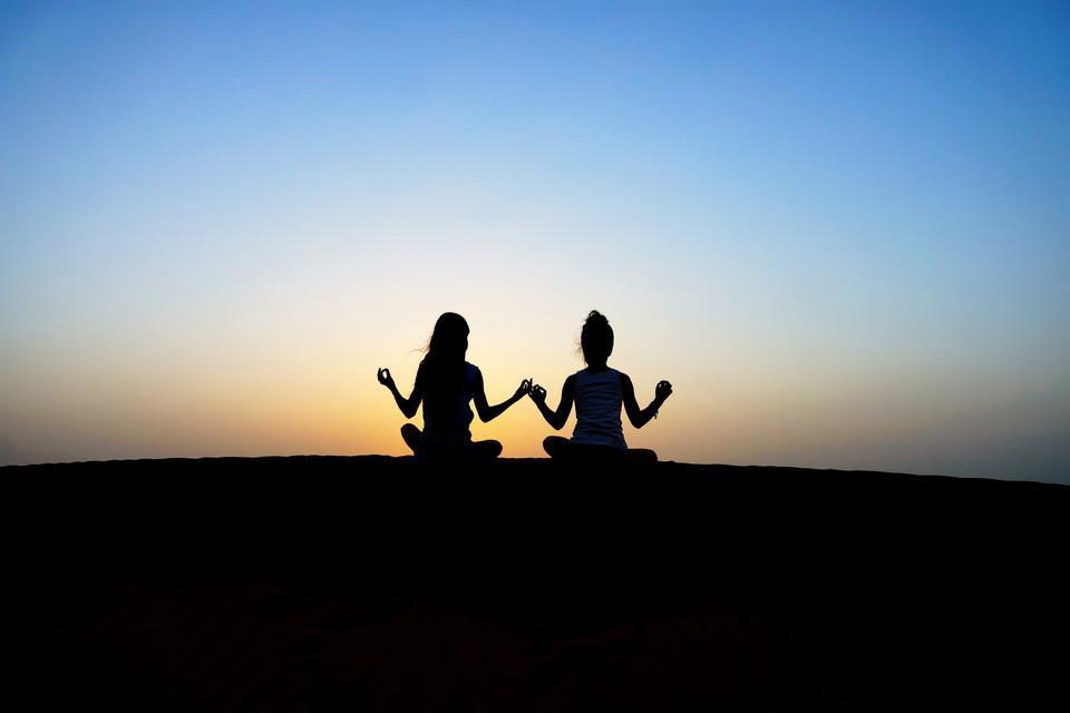 Zwei Frauen sitzen auf einem Fels im Sonnenuntergang