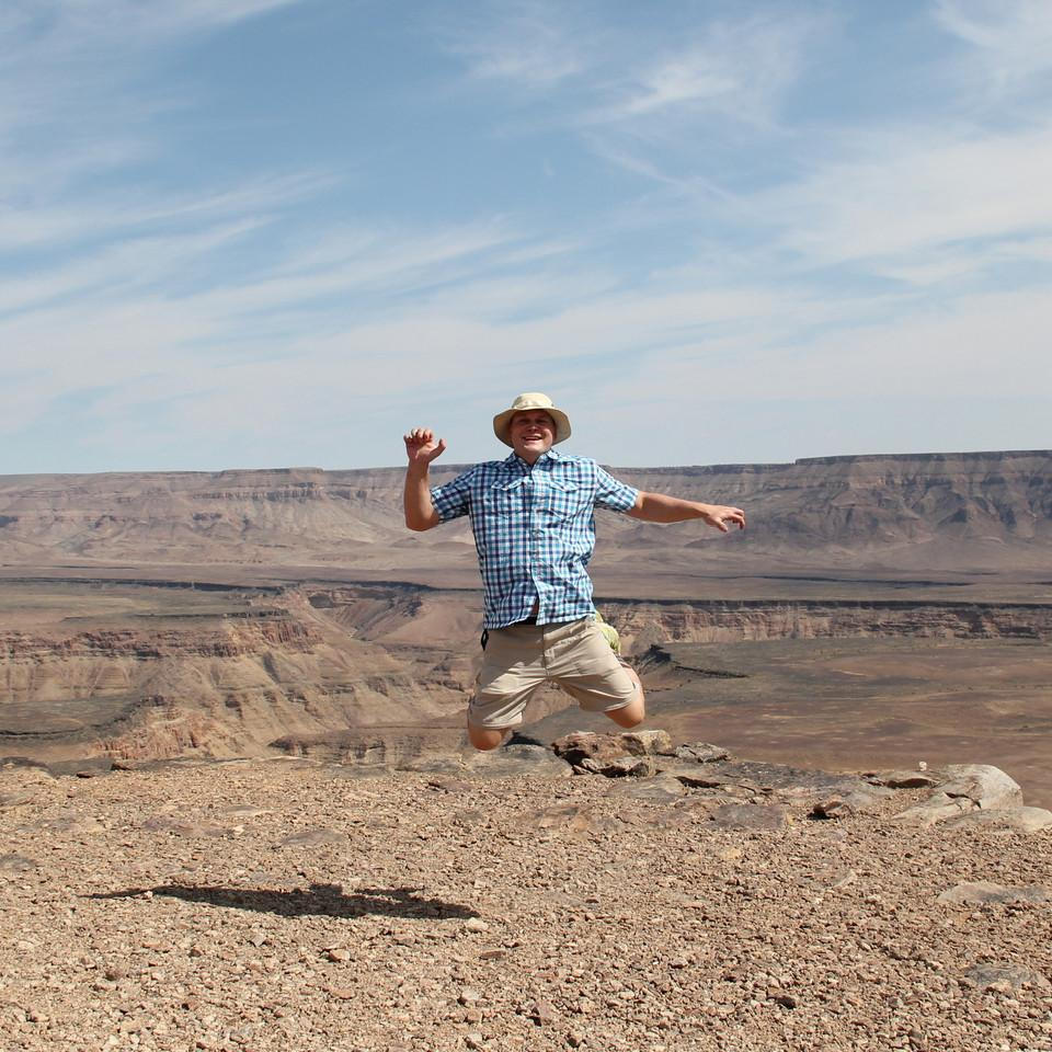 Mann springt in die Luft vor Wüstenlandschaft