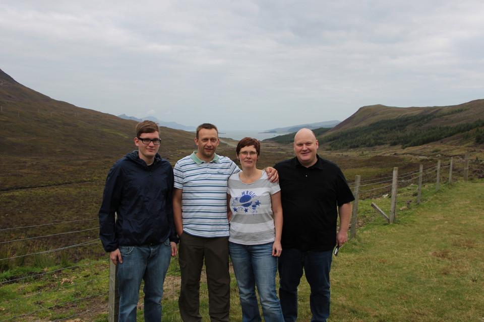 3 Männer und eine Frauen stehen vor grüner Landschaft