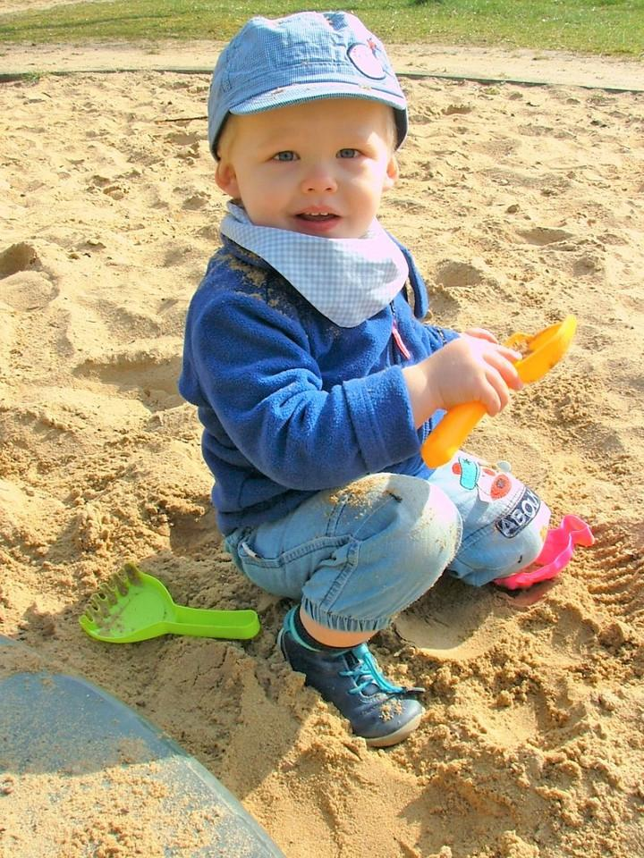 Kleiner blonder Junge spielt im Sandkasten