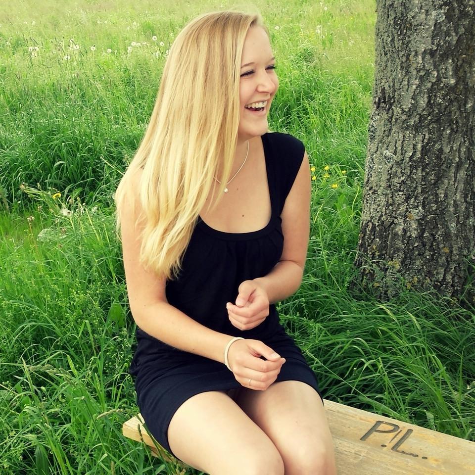 Blonde lachende junge Frau auf einer Bank