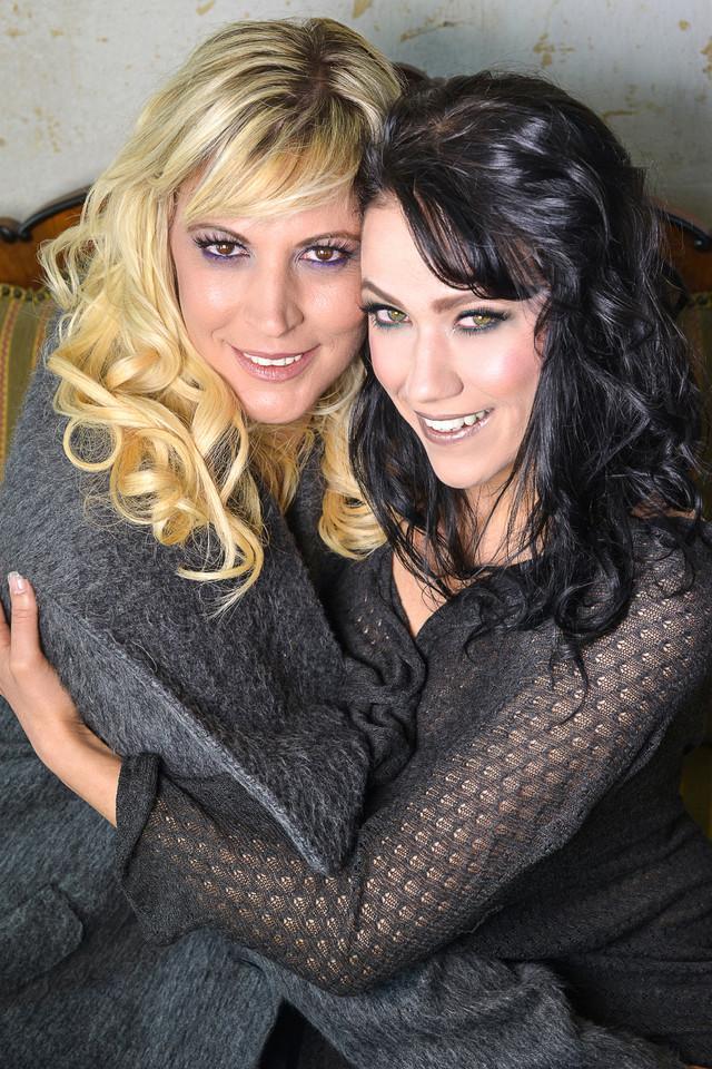 Eine blonde und brunette Frau haben sich im Arm